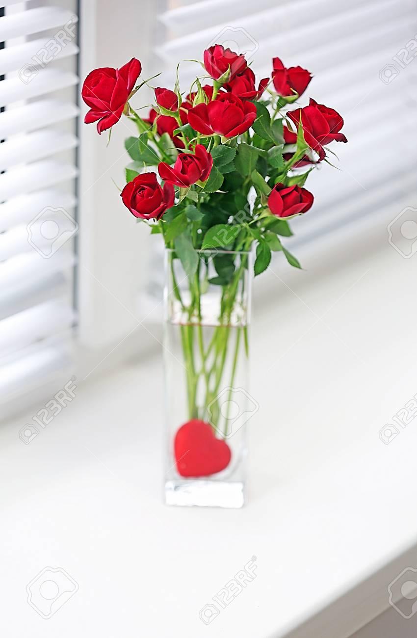 Bouquet De Roses Rouges Dans Un Vase De Verre Avec Le Coeur Sur Fond
