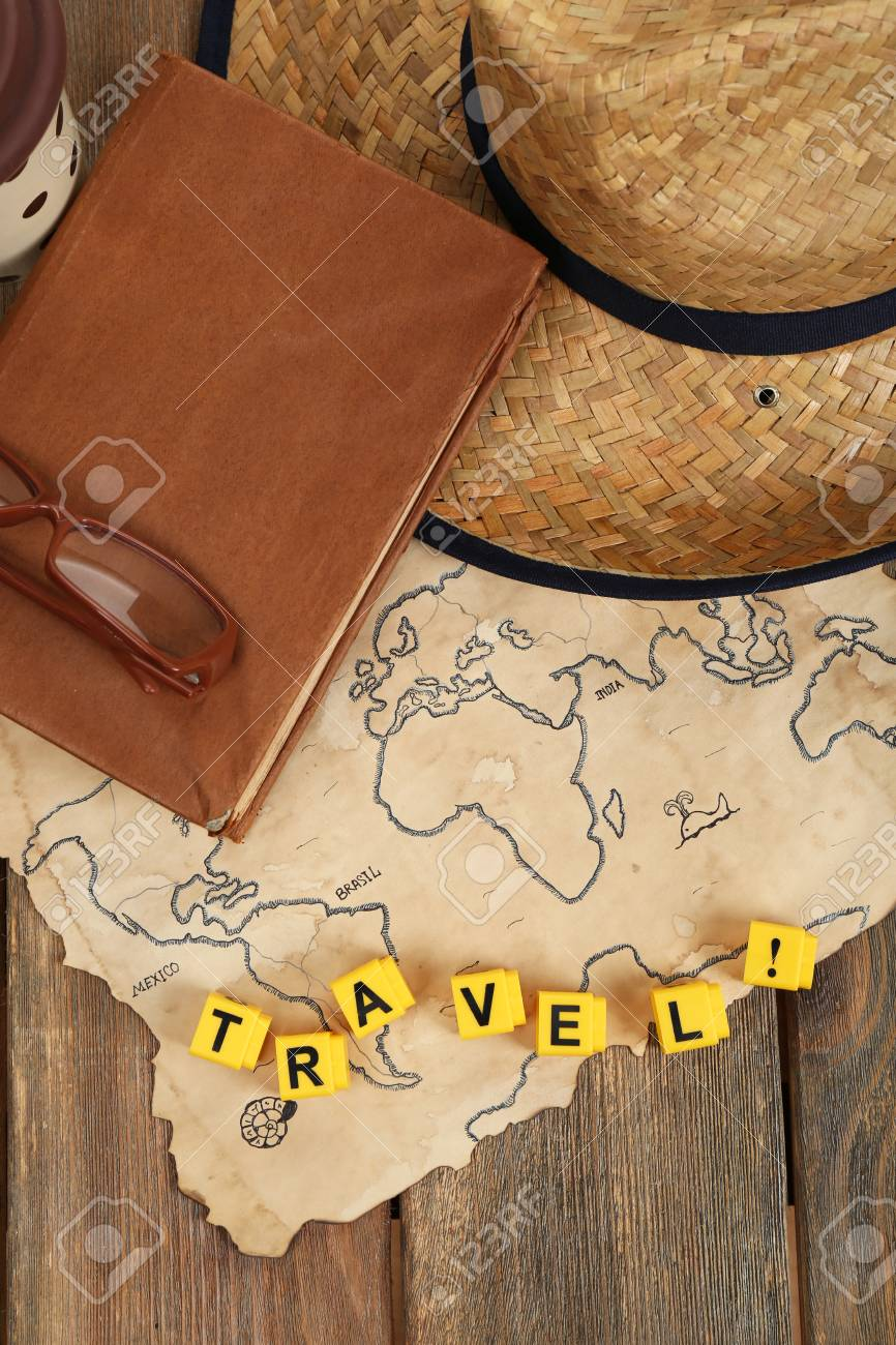 Straw hat, book and glasses with word Travel on world map and..