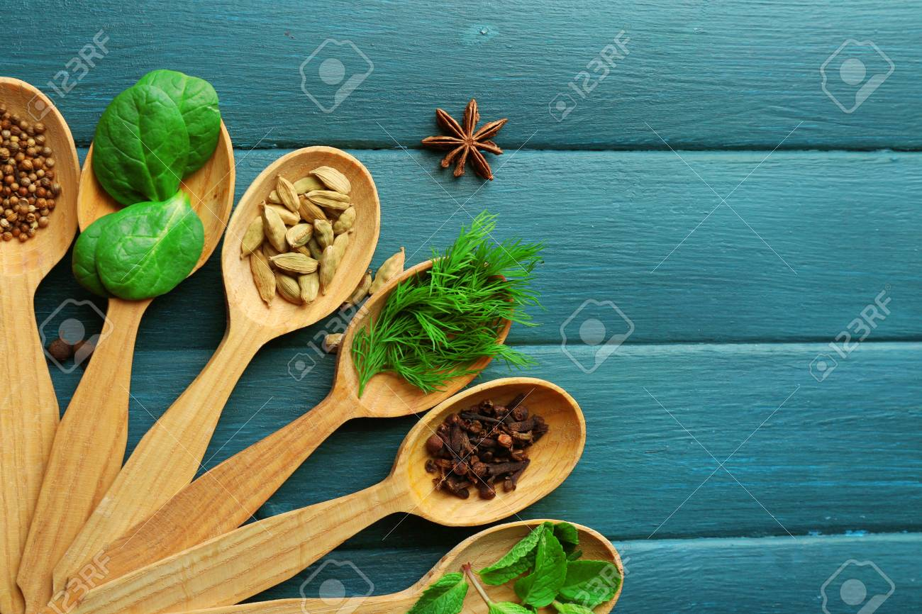 Wooden Spoons With Fresh Herbs And Spices On Color Wooden Background ...