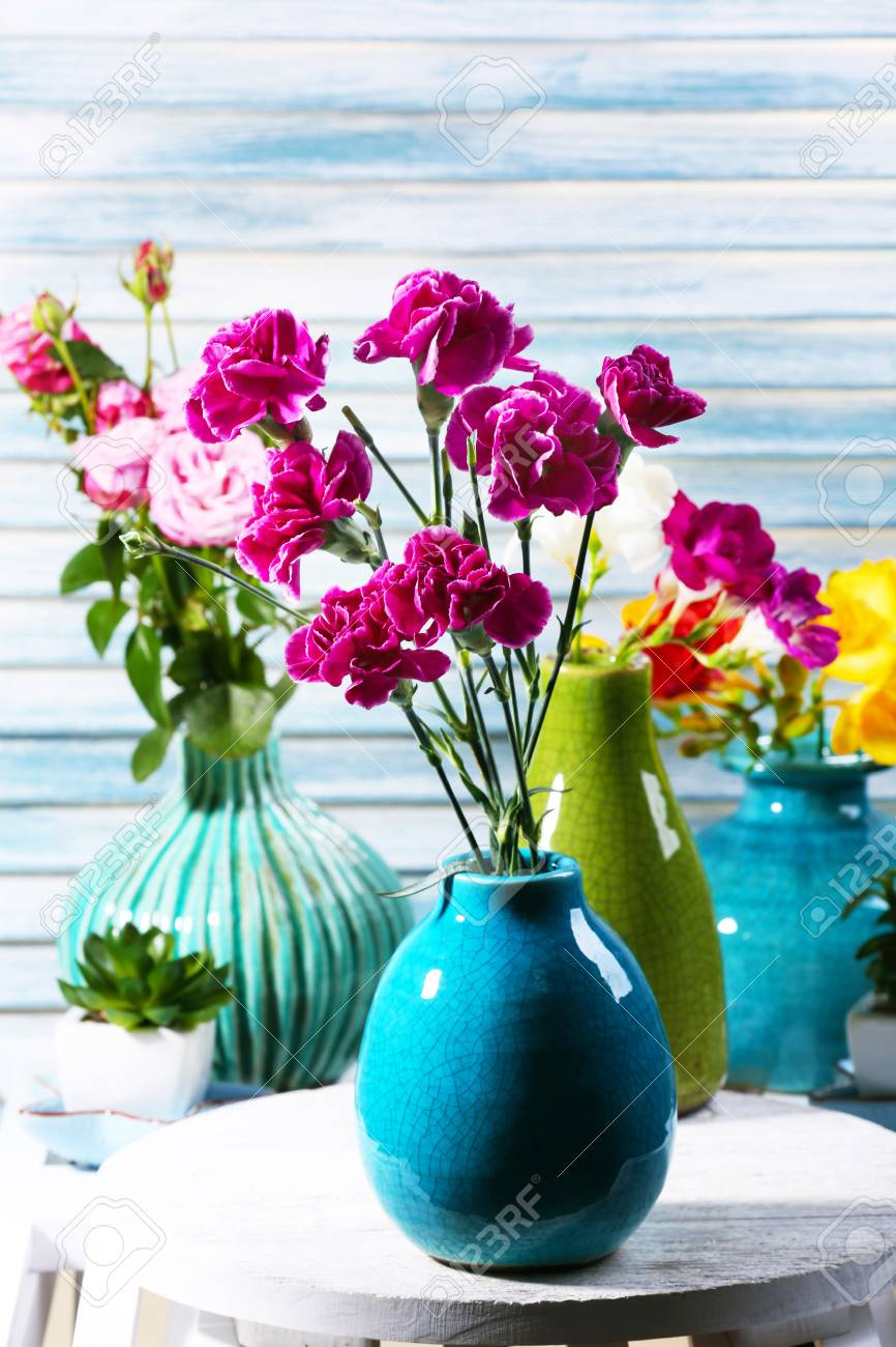 Different beautiful flowers in vases on wooden background stock different beautiful flowers in vases on wooden background stock photo 49619540 izmirmasajfo