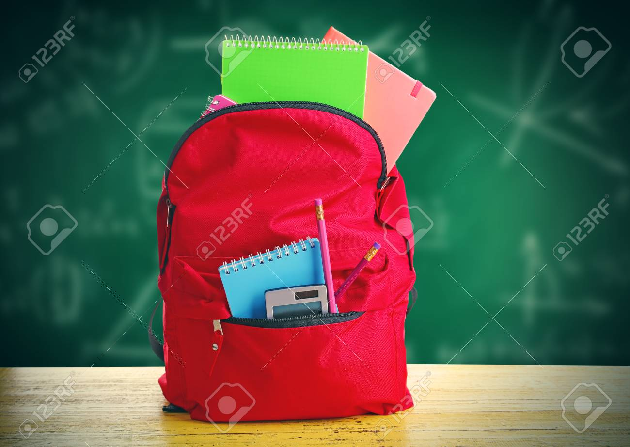 Red bag with school equipment on wooden table, near blackboard - 52076246