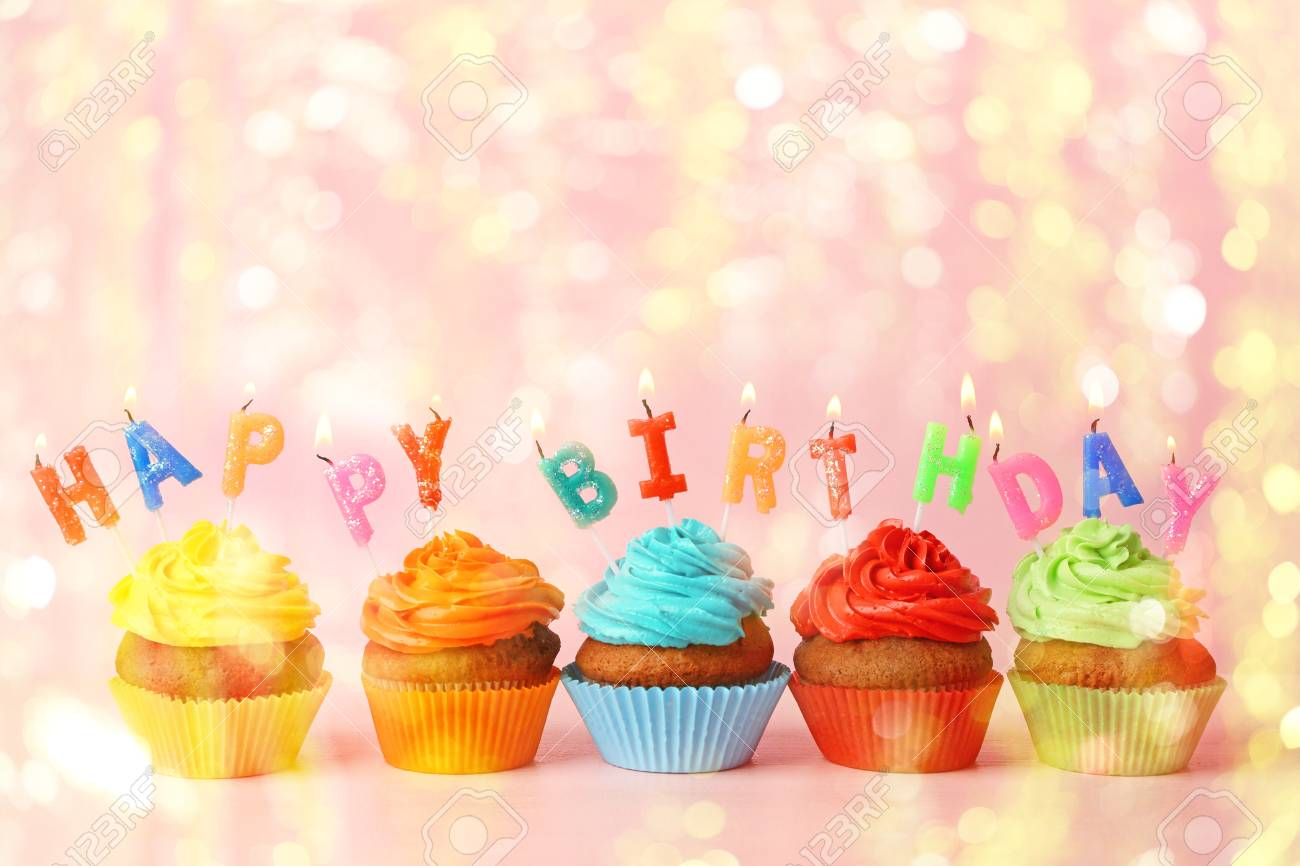 Rainbow Cupcakes With HAPPY BIRTHDAY Candles On Color Background Stock Photo