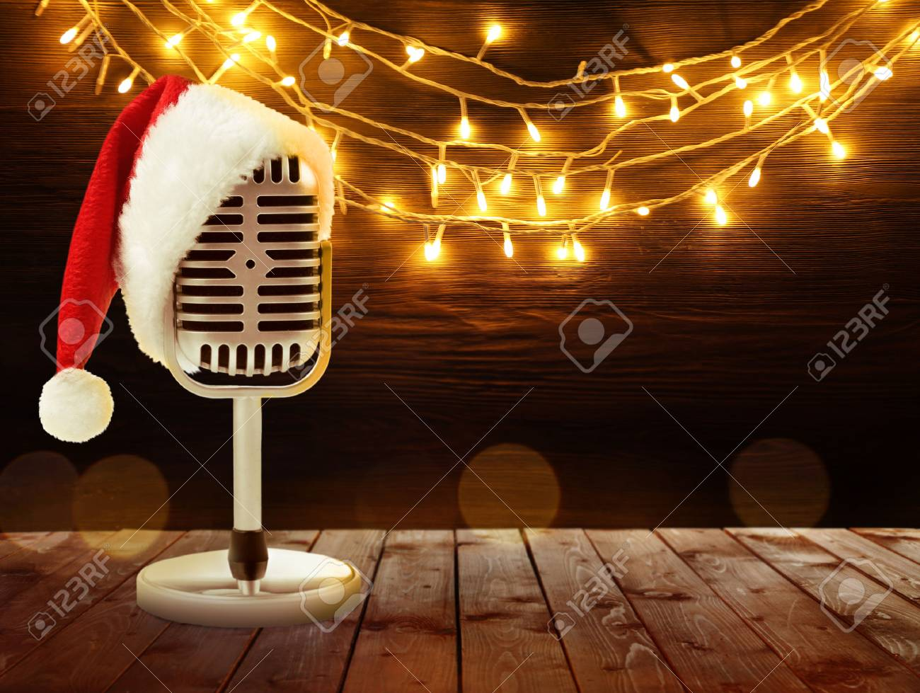 f7c5319ea936d Microphone with Santa hat and garland on background. Christmas music concept  Stock Photo - 90582092