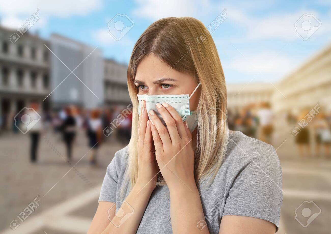Health care concept. Young woman in face mask on city street - 107933588