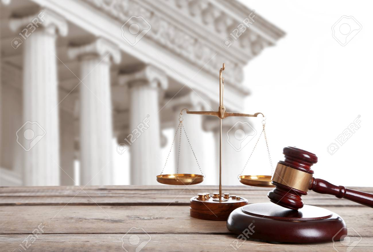 Judge's gavel with scales and courthouse on background. Concept of law - 92121521