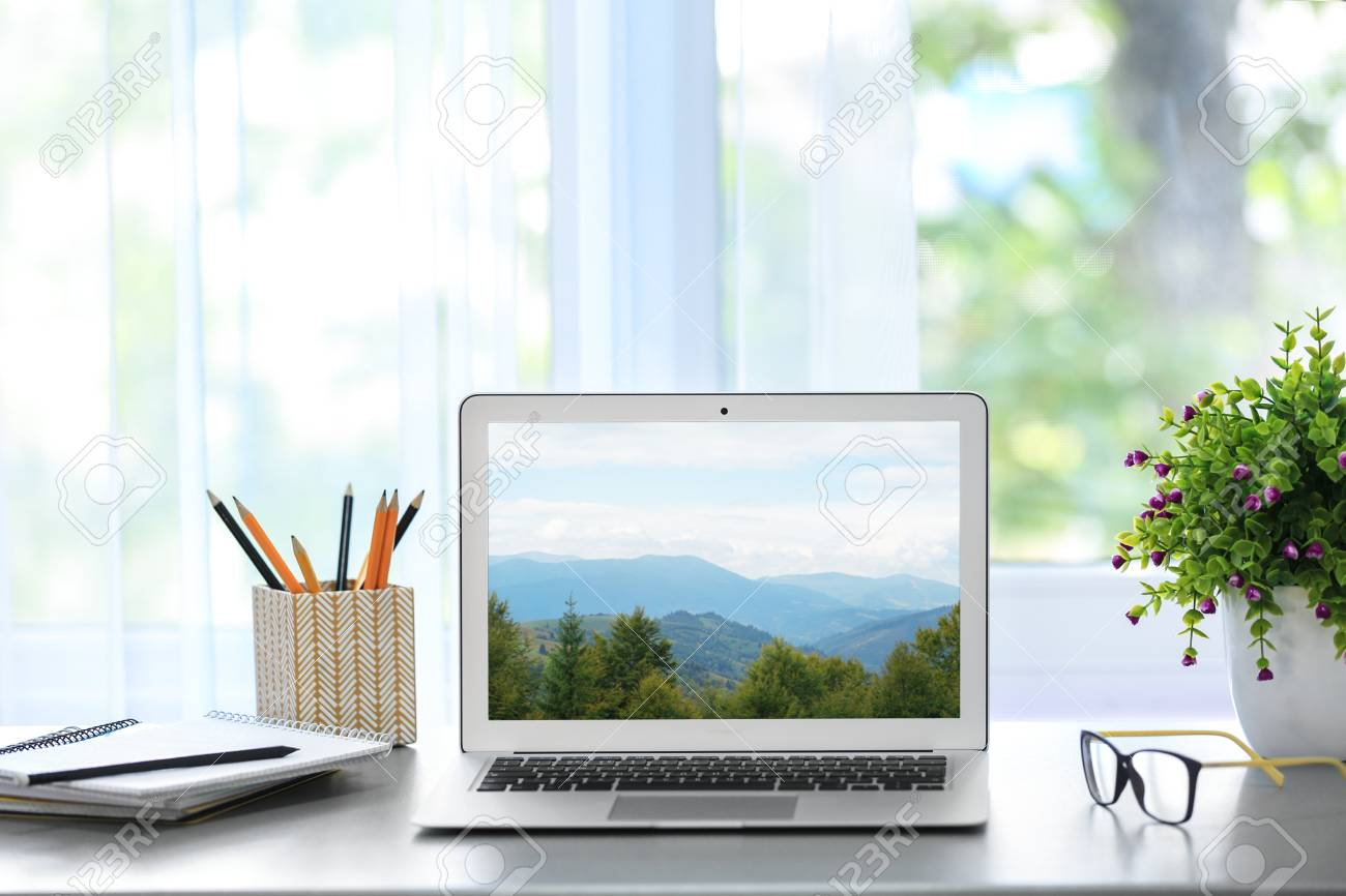 Stock Photo - Workplace with laptop and wallpaper of landscape on screen
