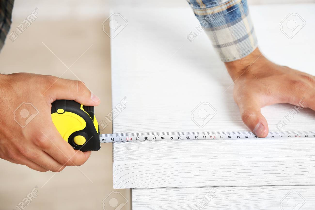Stock Photo   Young Man Measuring Home Furniture With Measure Tape, Close Up