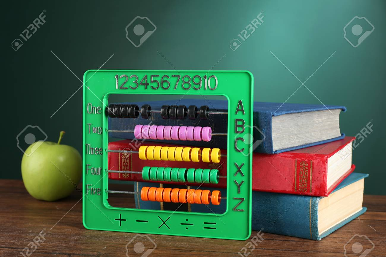 Colorful Abacus With Stack Of Book Sand Green Apple On Desk Chalkboard Background Stock
