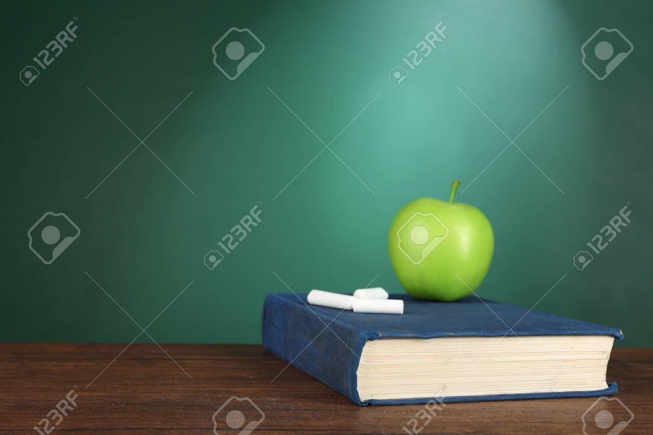 Book With Green Apple And Pieces Of Chalk On Chalkboard Background Stock Photo