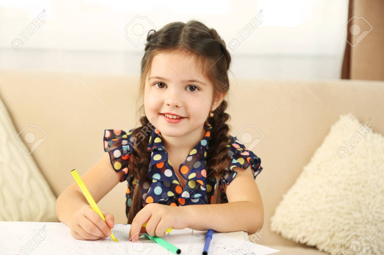Cute little girl doing her homework, close-up, on home interior background - 95469402