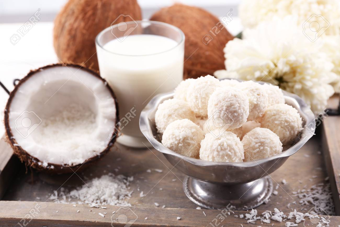 Homemade sweets in coconut flakes and fresh coconut on tray,
