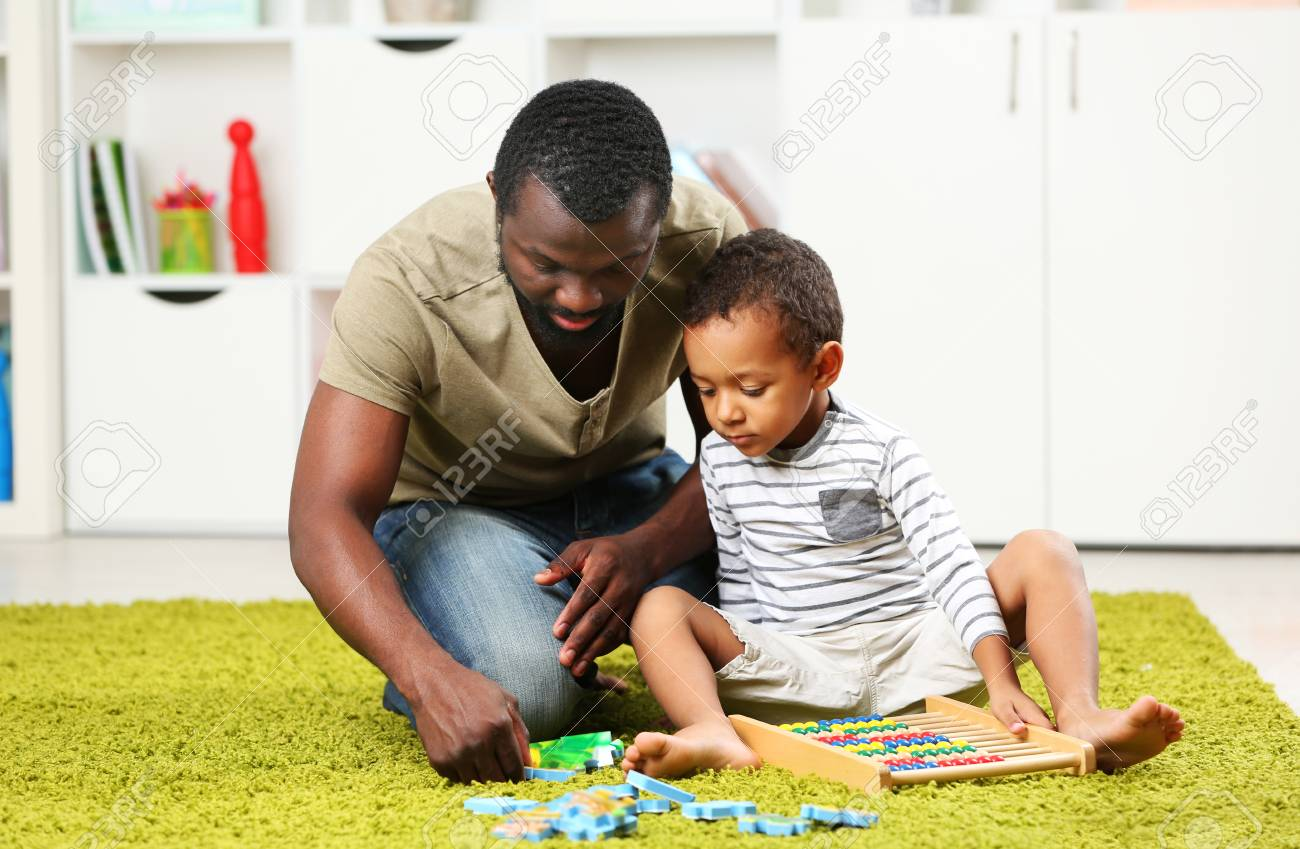 Father and son playing in the children room - 95369003