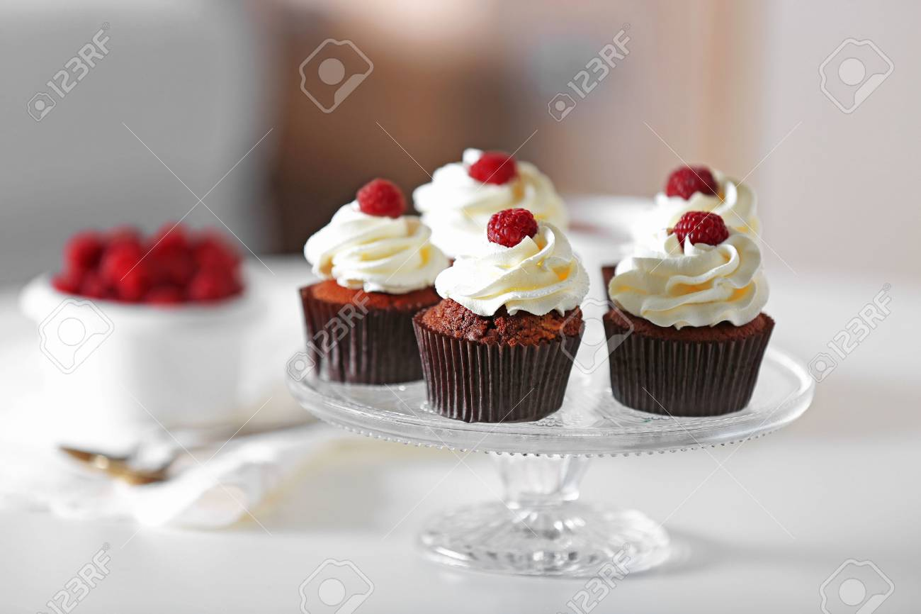 Beautiful Chocolate Cupcakes With Cream And Raspberry On Table Stock