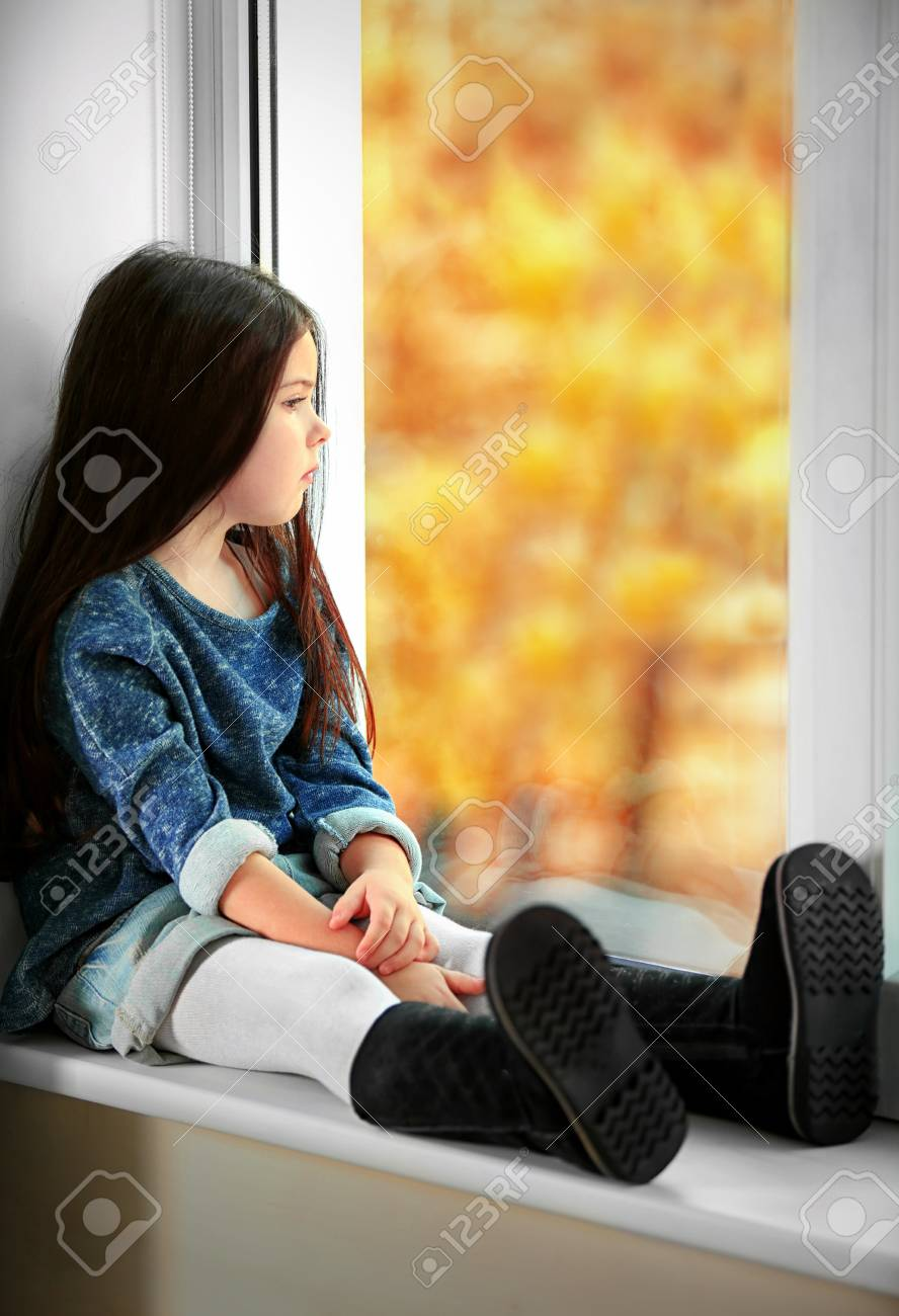 Little Girl Waiting For Someone And Looking Out The Window Stock