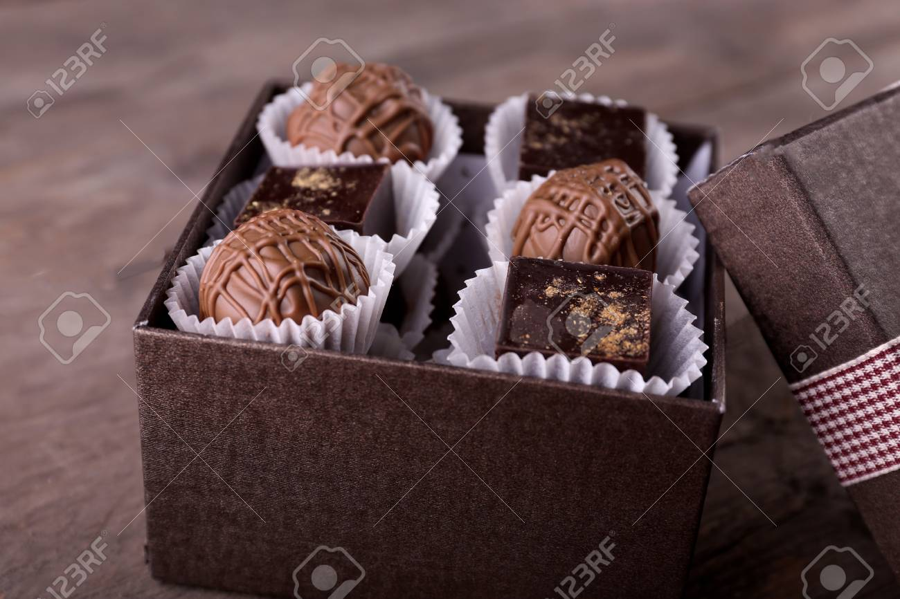 Delicious Chocolate Candies In Beautiful Gift Box On Wooden