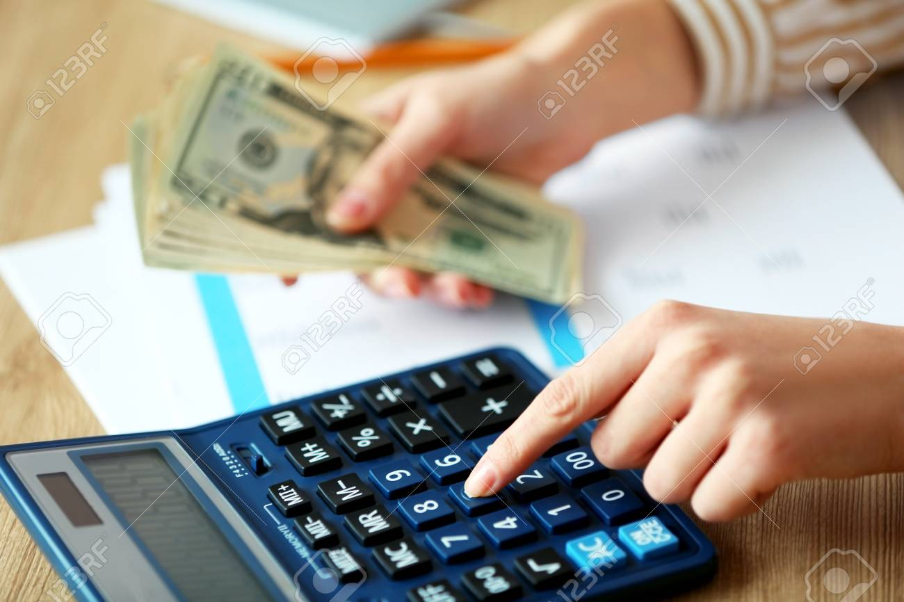 woman counting money and working on calculator at the table stock