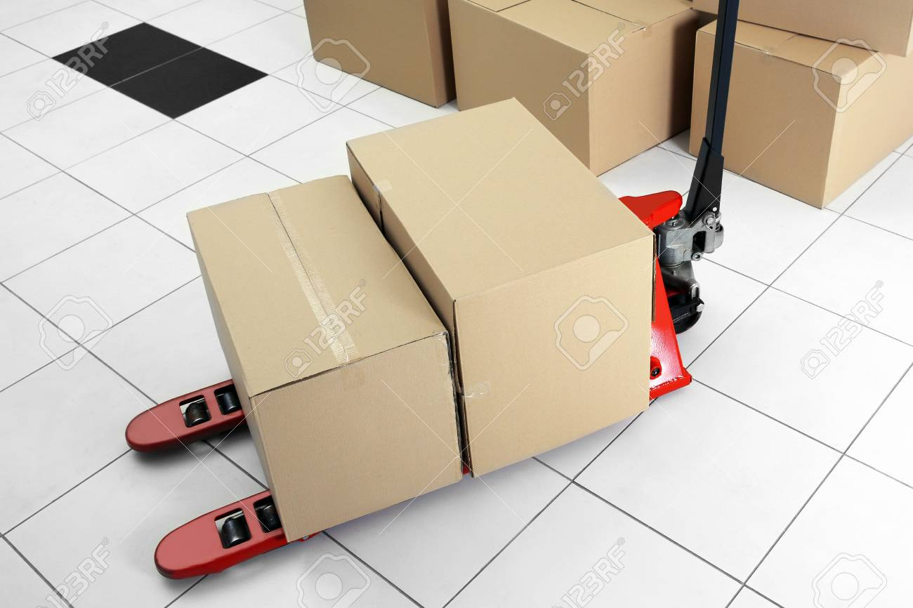 Manual pallet truck with carton boxes indoors Stock Photo - 95959064