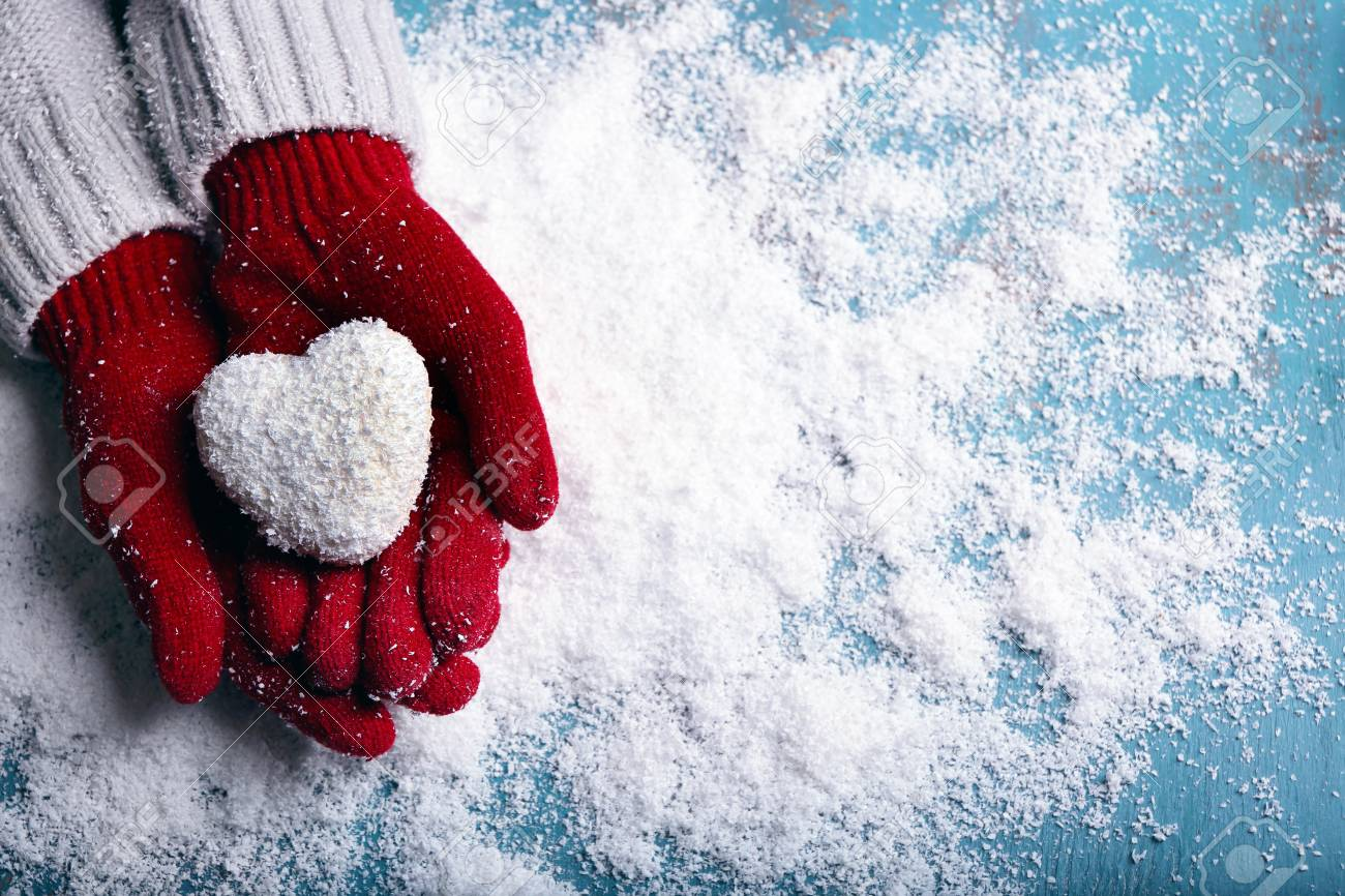 Female hands in mittens with decorative heart on snow background - 95473664