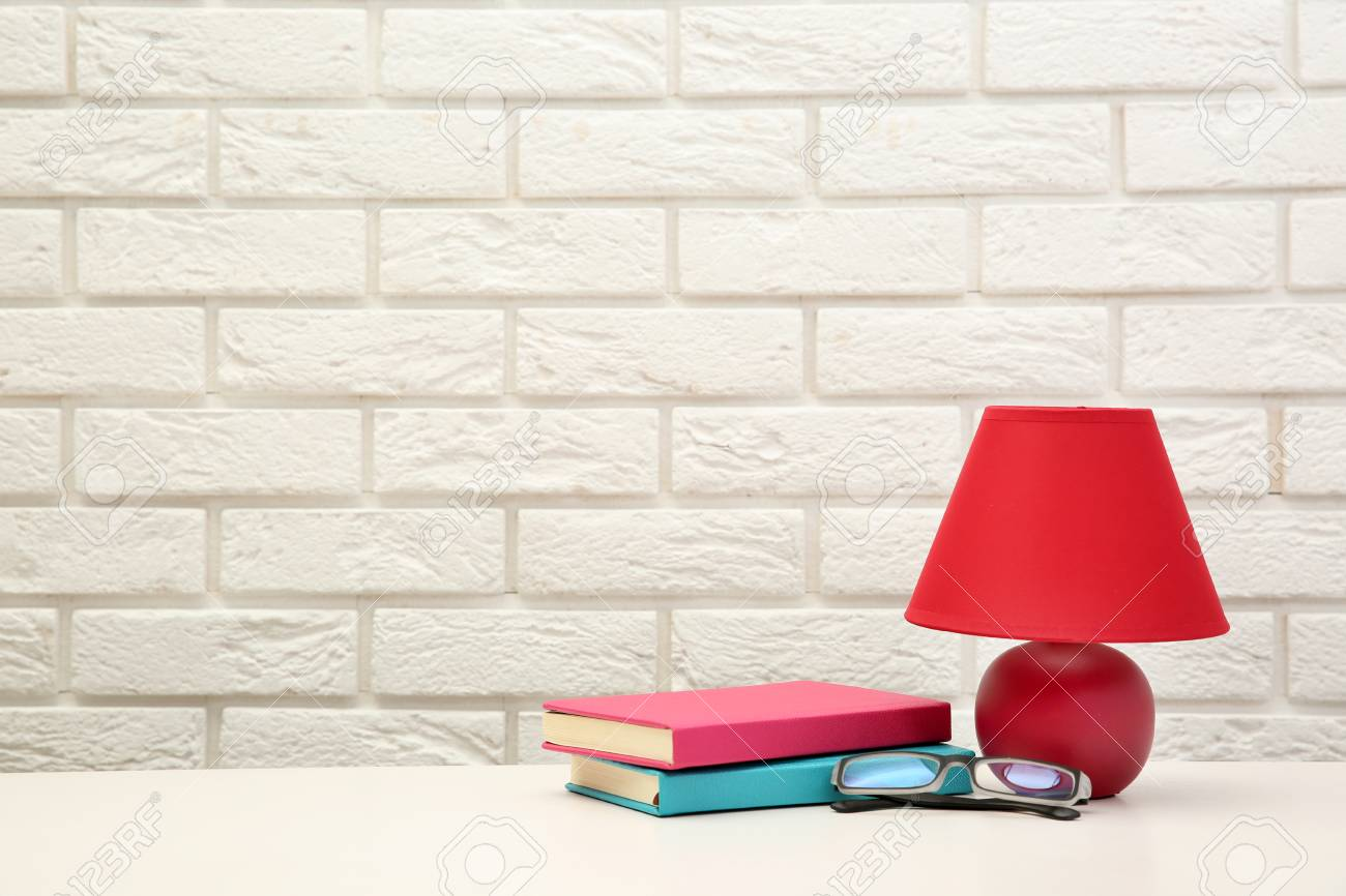 Night Lamp And Home Decor On The Desk On Brick Wall Background Stock
