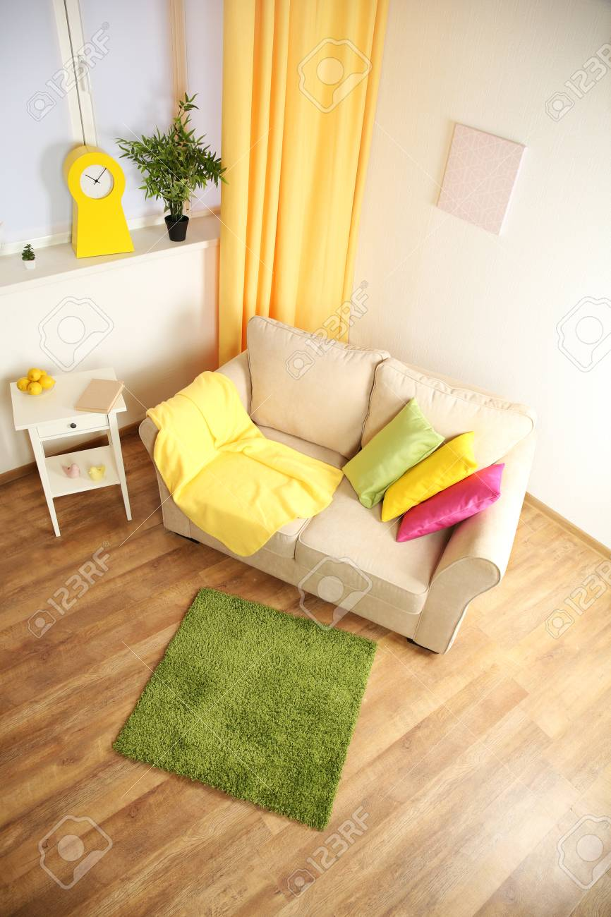 Modern living room interior with beige sofa and small green carpet stock photo 95592411