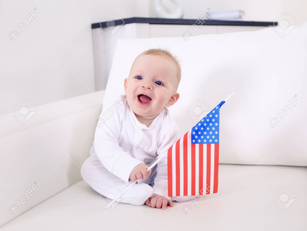 Astounding Cute Baby Boy On White Couch With American Flag Closeup Dailytribune Chair Design For Home Dailytribuneorg