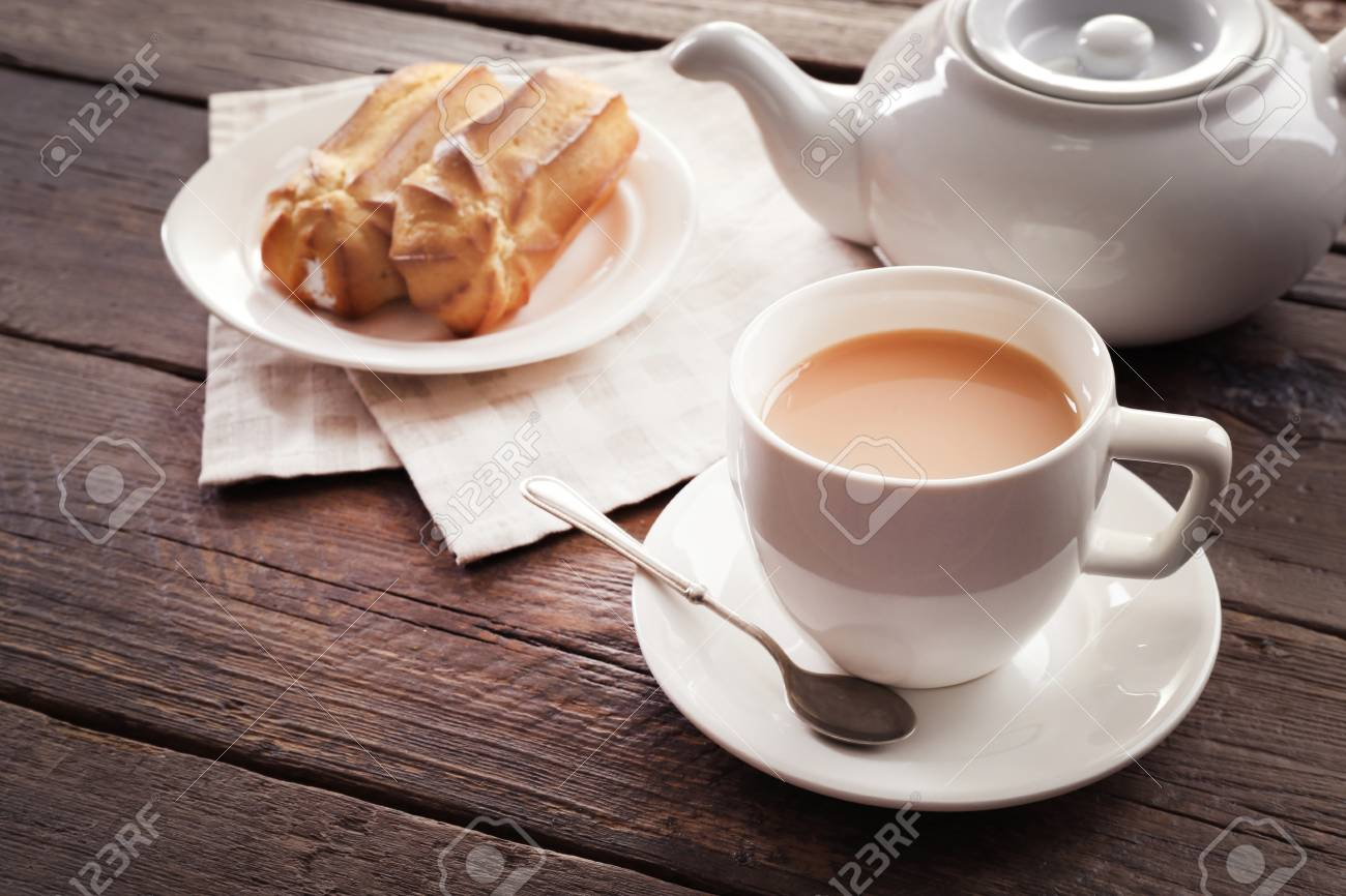Milk tea with eclairs on wooden background