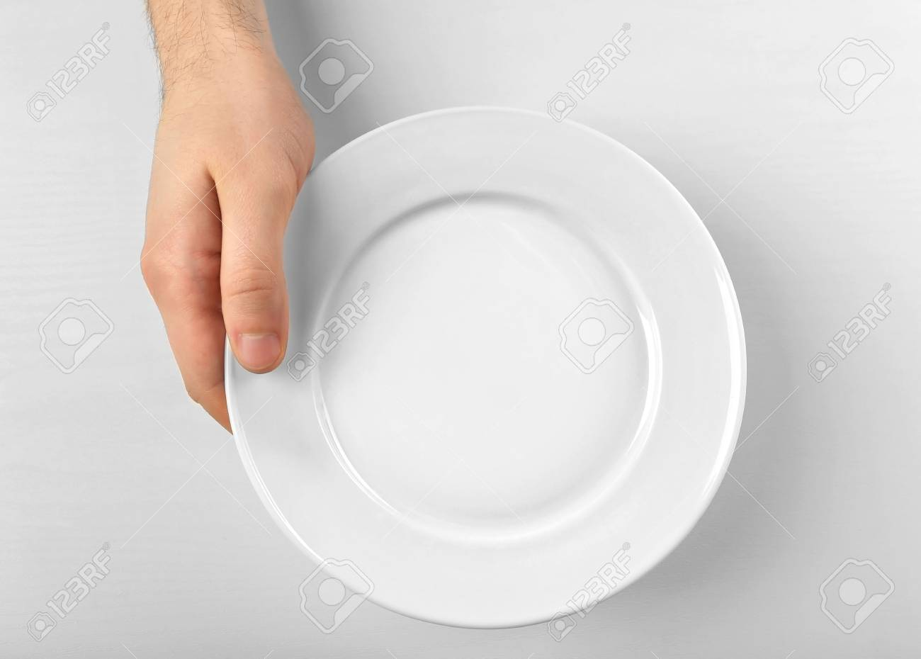 Male hand holding white plate, isolated on white - 95730159
