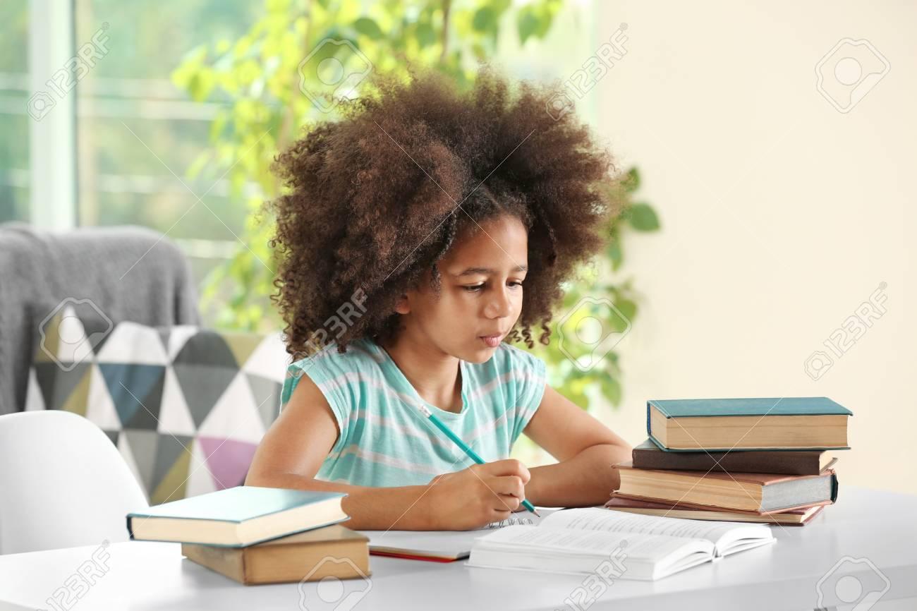 Cute African girl doing homework - 96715116