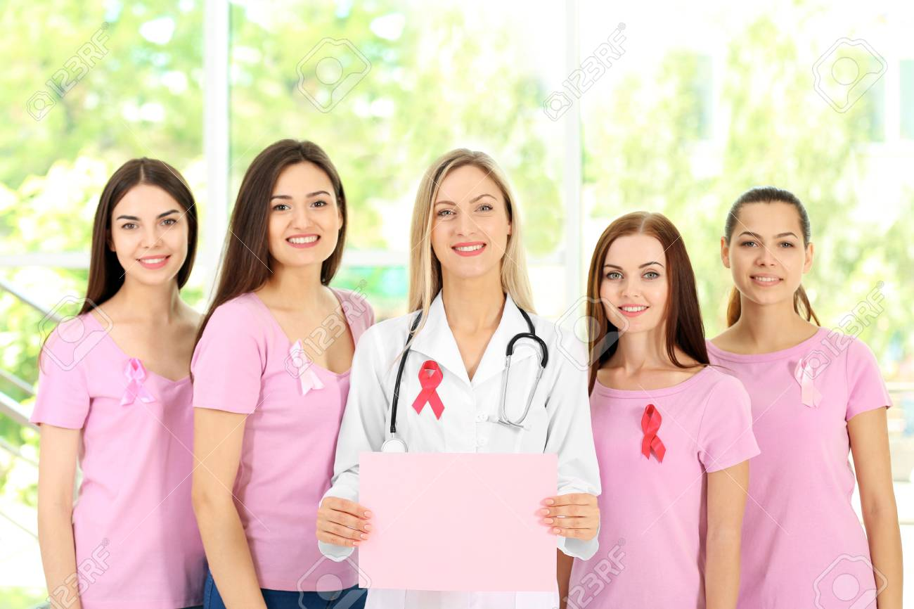 Female doctor and girls with pink ribbon. Breast cancer concept Stock Photo  - 97864741