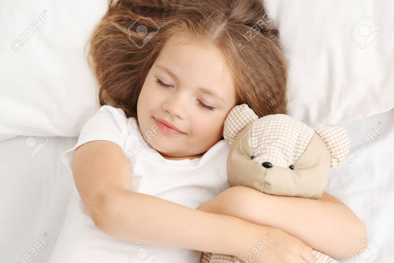 77d0cad2af18 Cute little girl sleeping with teddy bear in bed Stock Photo - 96568753