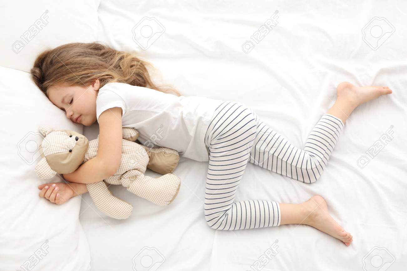 Cute little girl sleeping with teddy bear in bed - 96568762