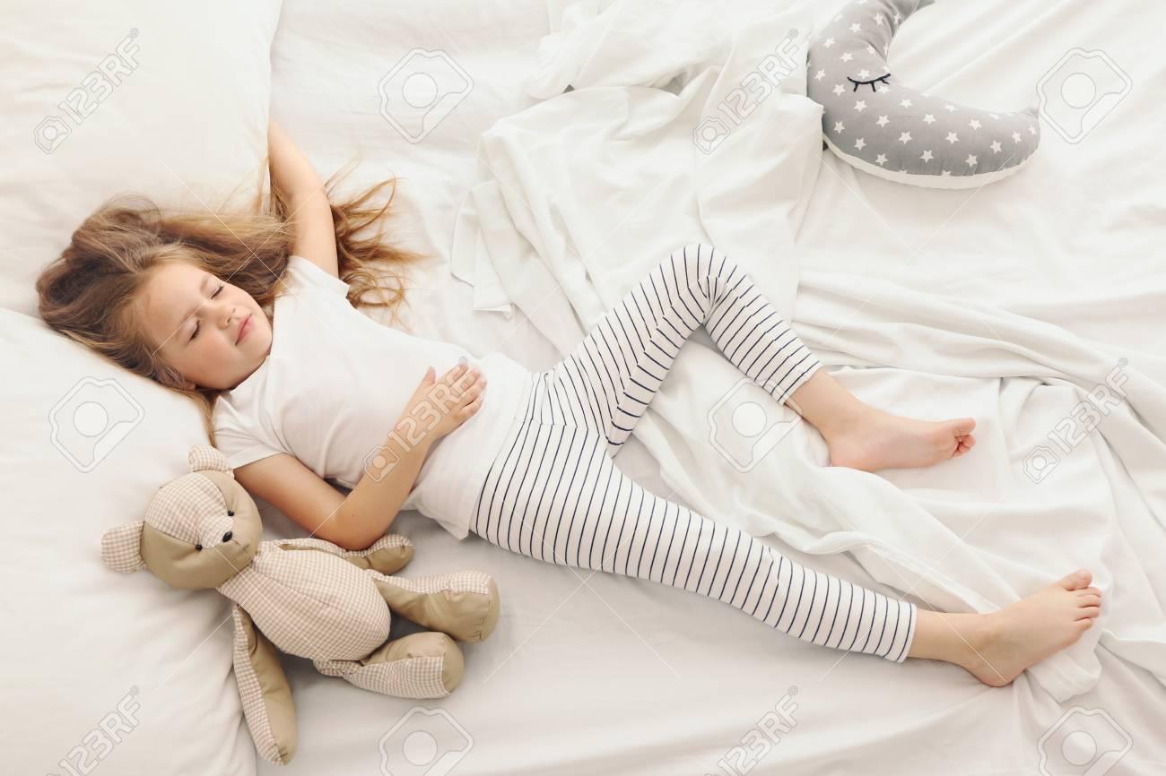 e4fc588aeb7c Cute little girl sleeping with teddy bear in bed Stock Photo - 96568763