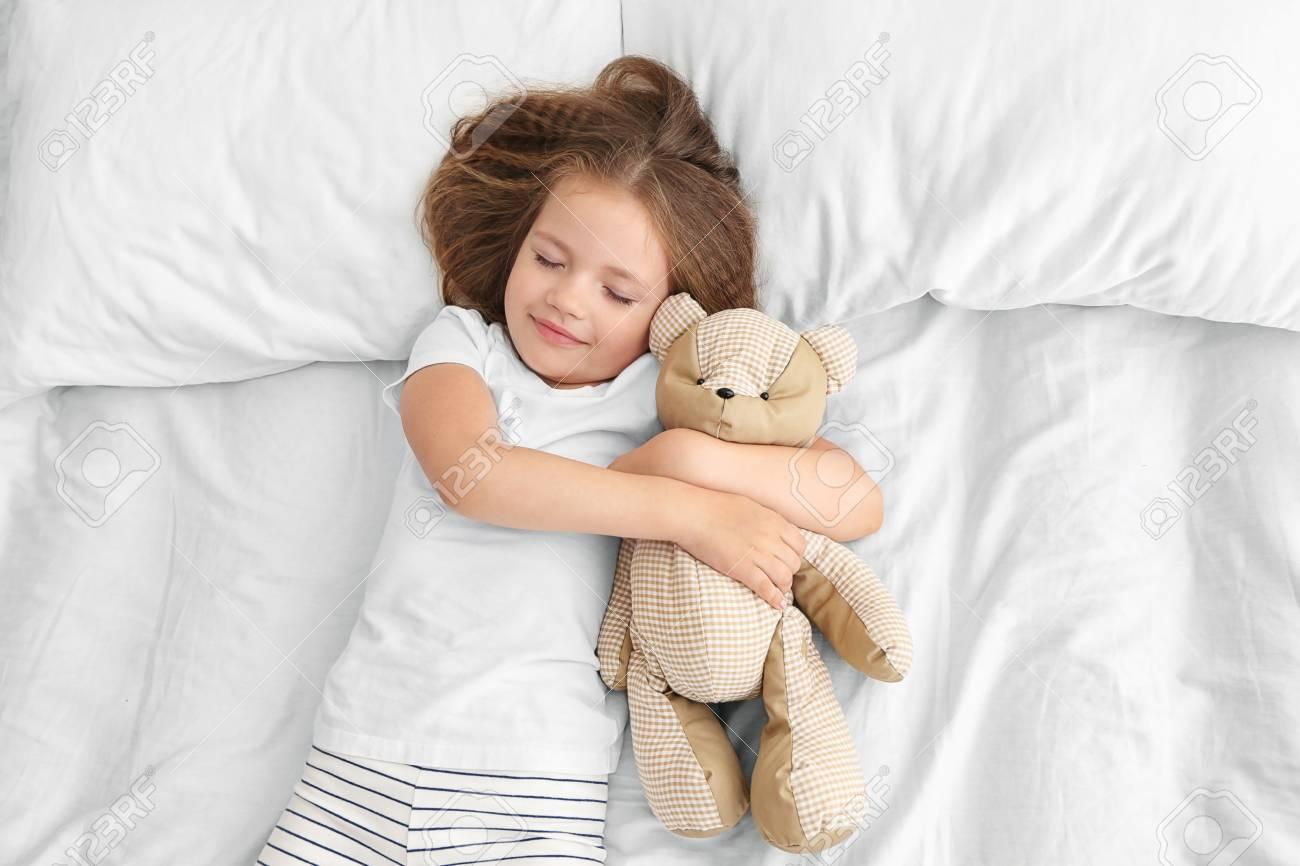 fc9db7efba03 Cute little girl sleeping with teddy bear in bed Stock Photo - 96568846