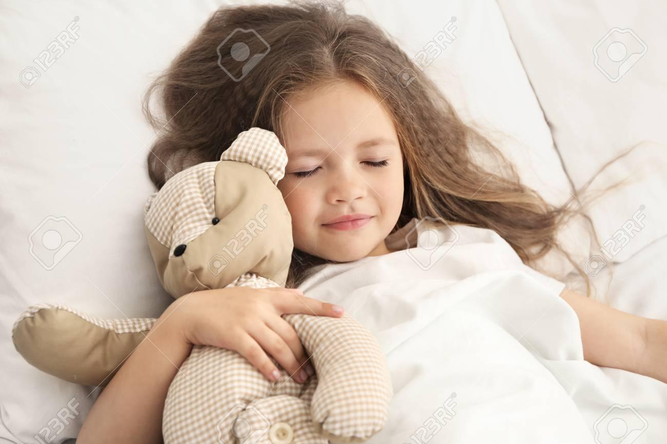 7beaa83b193a Cute little girl sleeping with teddy bear in bed Stock Photo - 96570512