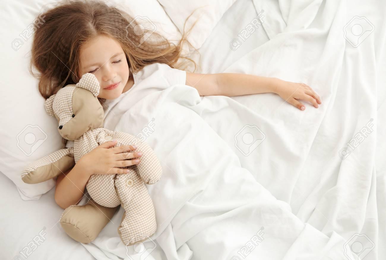 0975b5efc733 Cute little girl sleeping with teddy bear in bed Stock Photo - 96569021