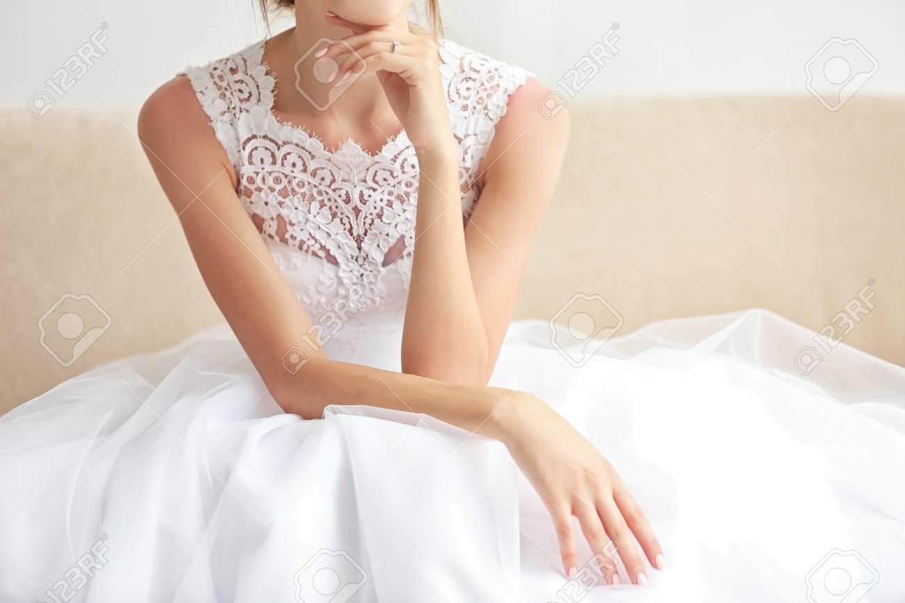 Braut Im Schonen Hochzeitskleid Das Auf Sofa Sitzt Lizenzfreie
