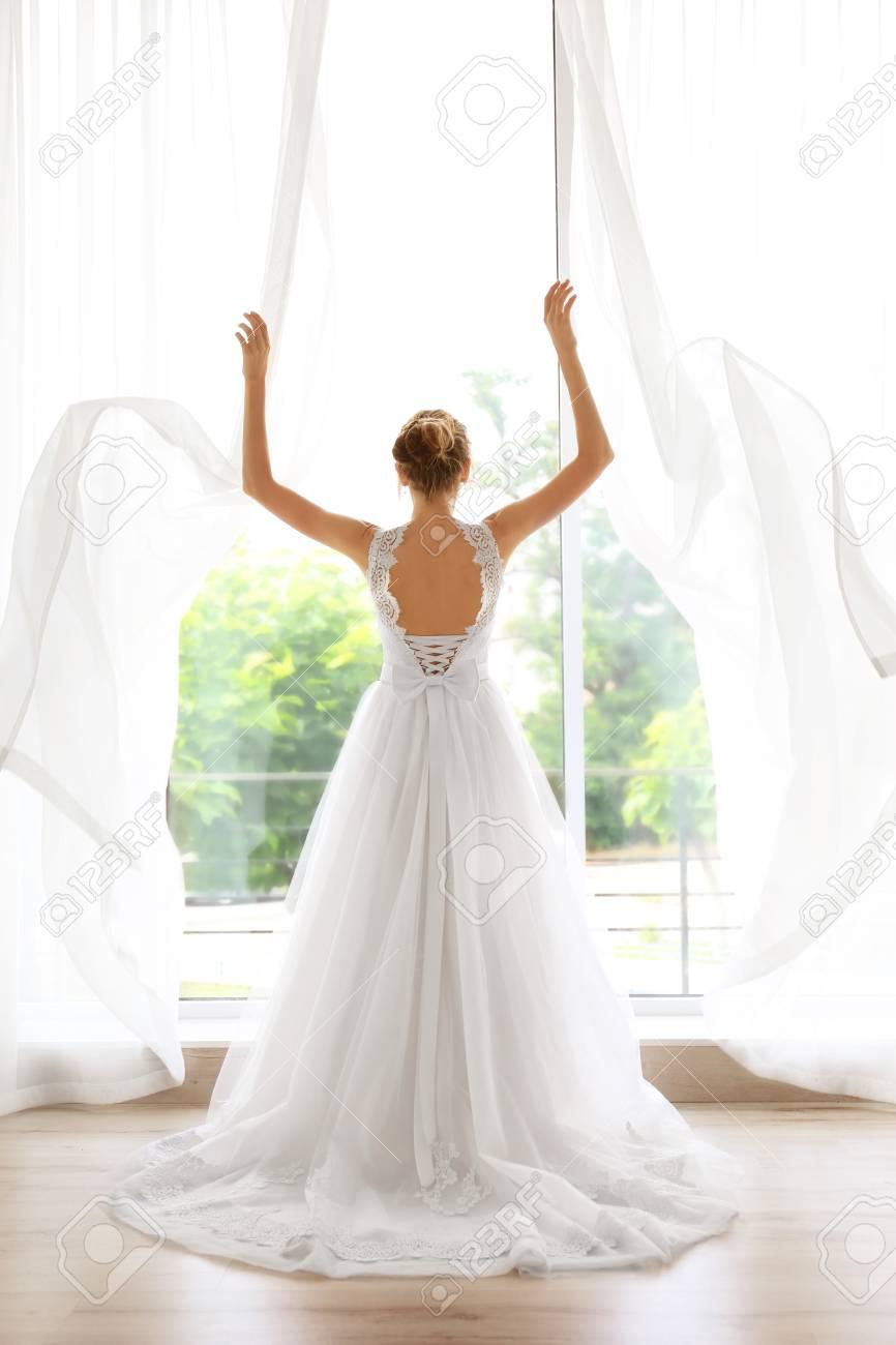 Braut In Einem Schonen Hochzeitskleid Das Nahe Fenster Steht