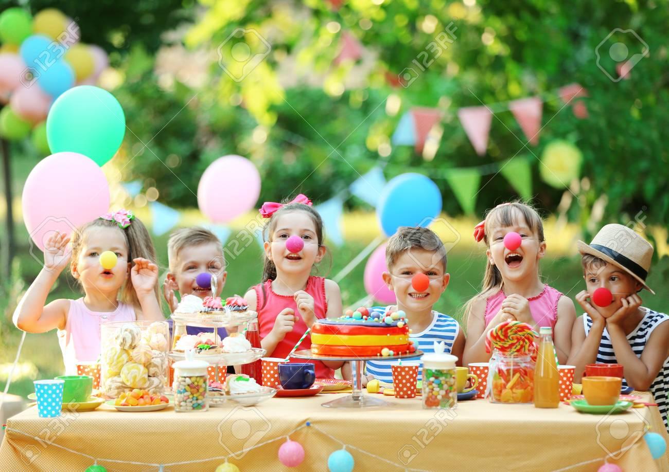 Children celebrating birthday in park - 96426727
