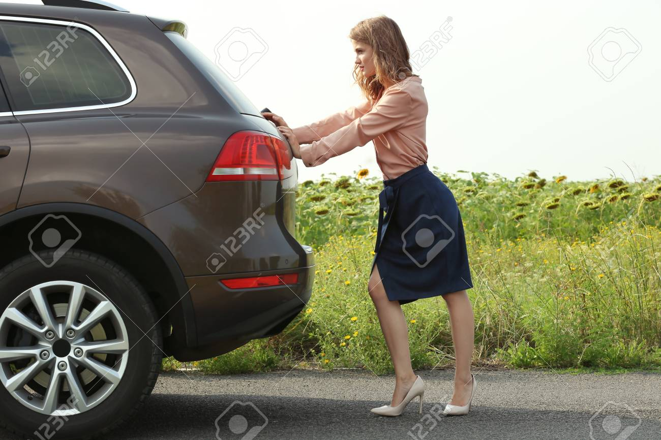 pretty young woman pushing car stock photo picture and royalty free