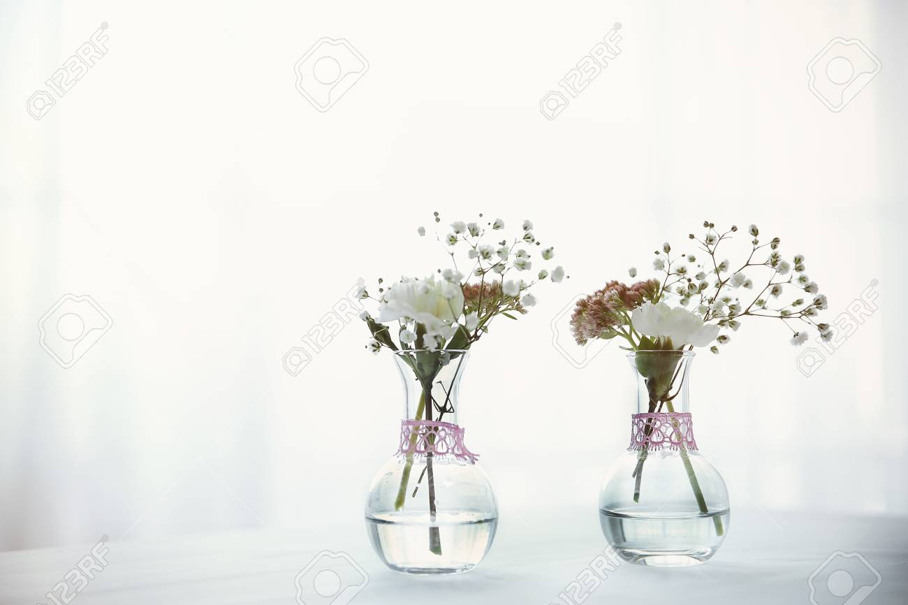 123RF.com & Mini glass vases with flowers on table