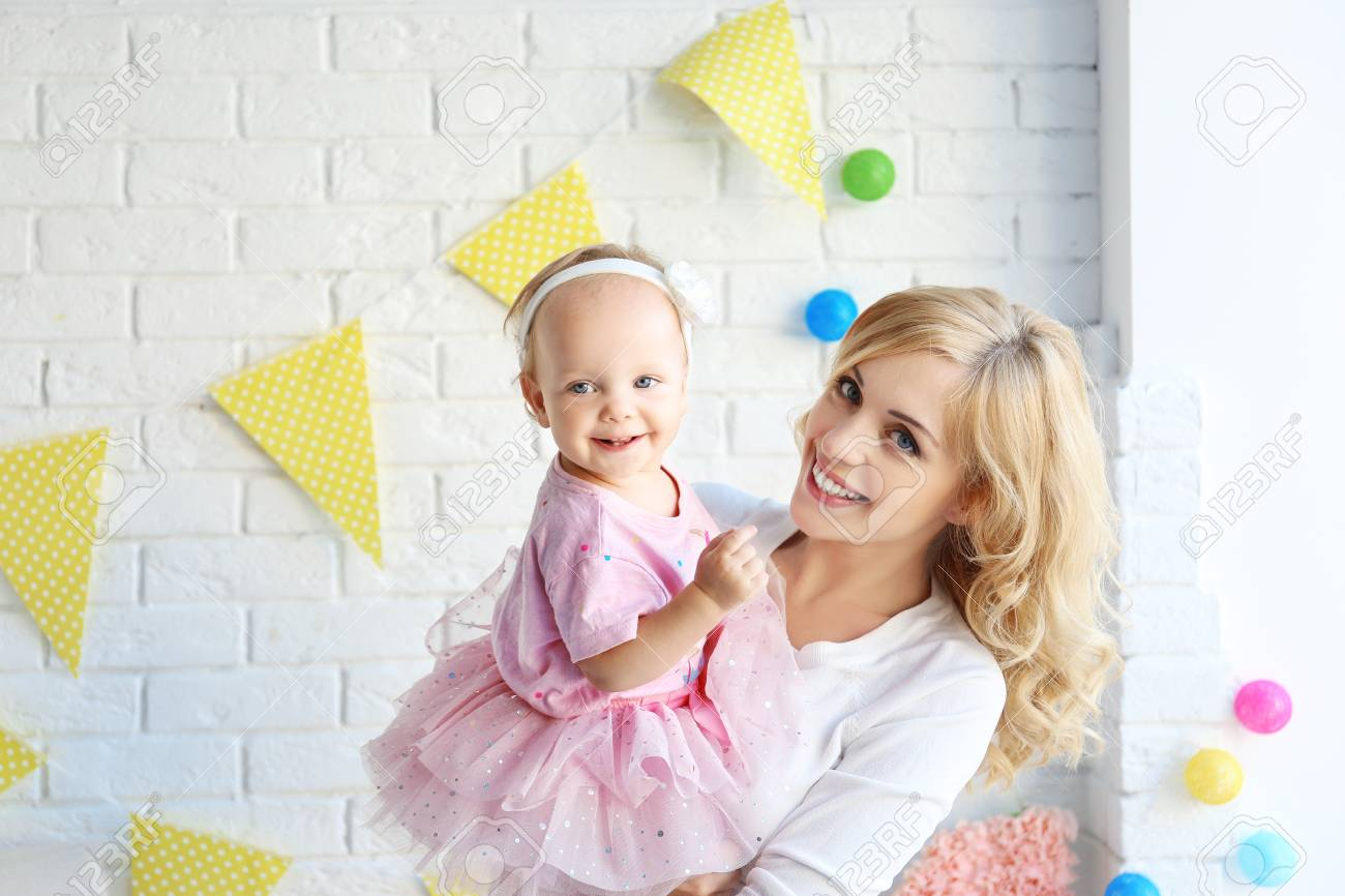 Portrait of happy mother and daughter on her first birthday party,