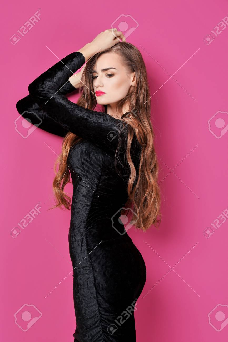 Gorgeous Young Woman In Black Evening Gown On Pink Background Stock ...