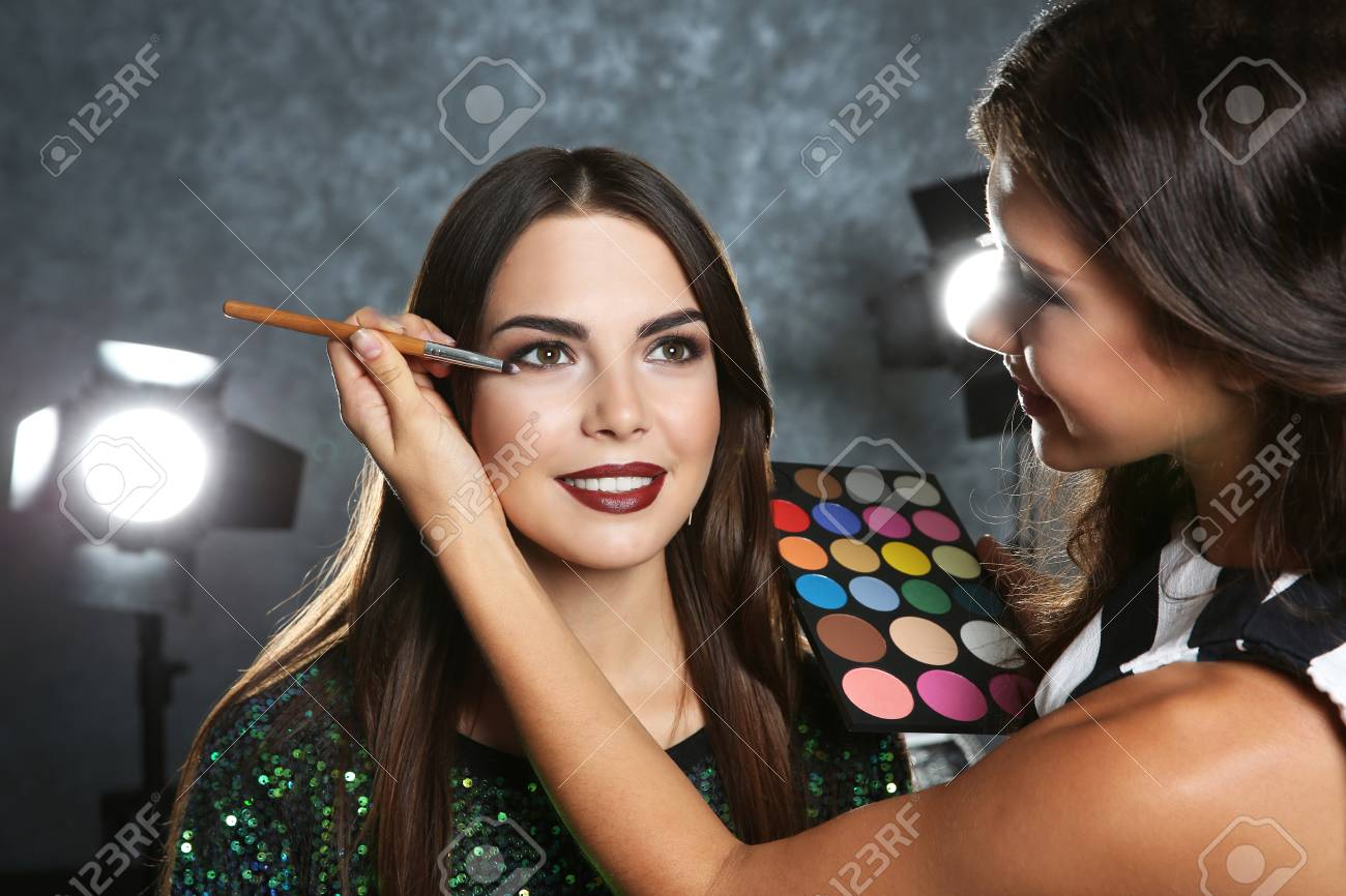 Professional Makeup Artist Working With Beautiful Young Woman Stock