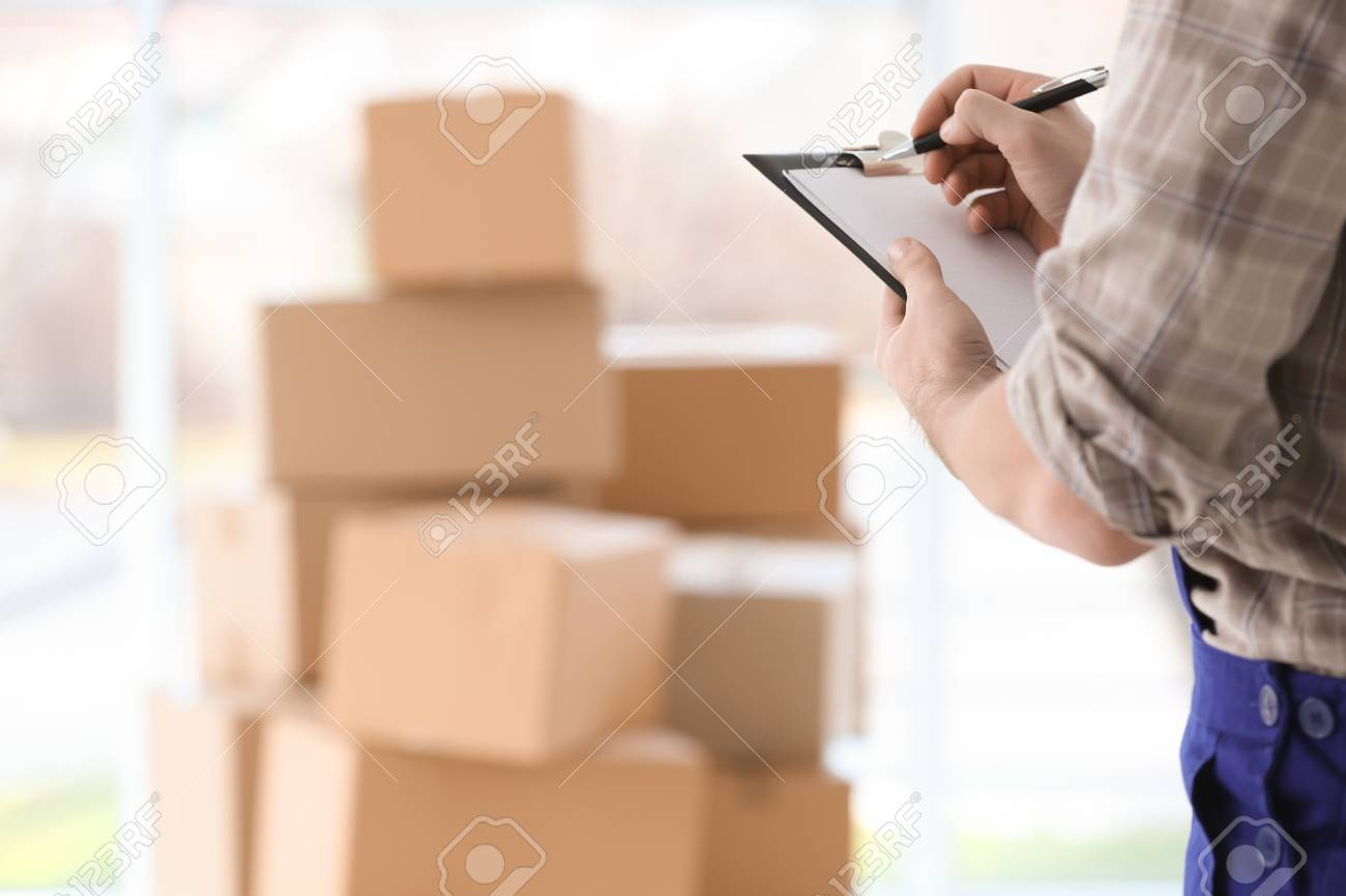 Man holding clipboard on blurred boxes background - 97297311