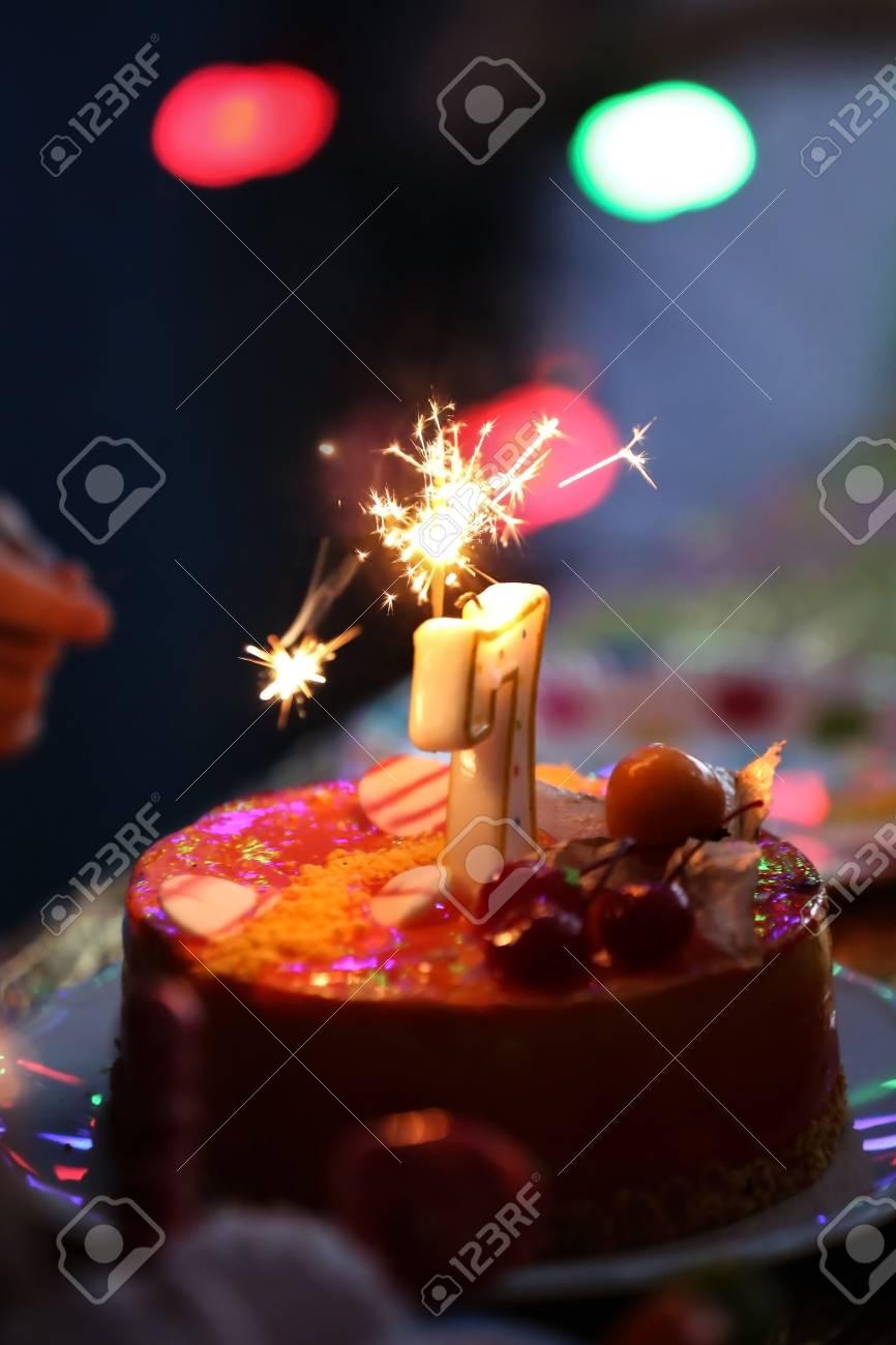 Tasty Birthday Cake With Sparkler On Table Against Defocused Stock