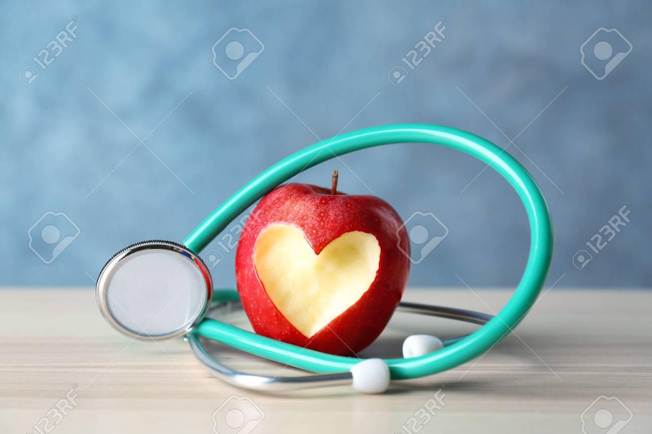 Apple with stethoscope on color background - 97430274