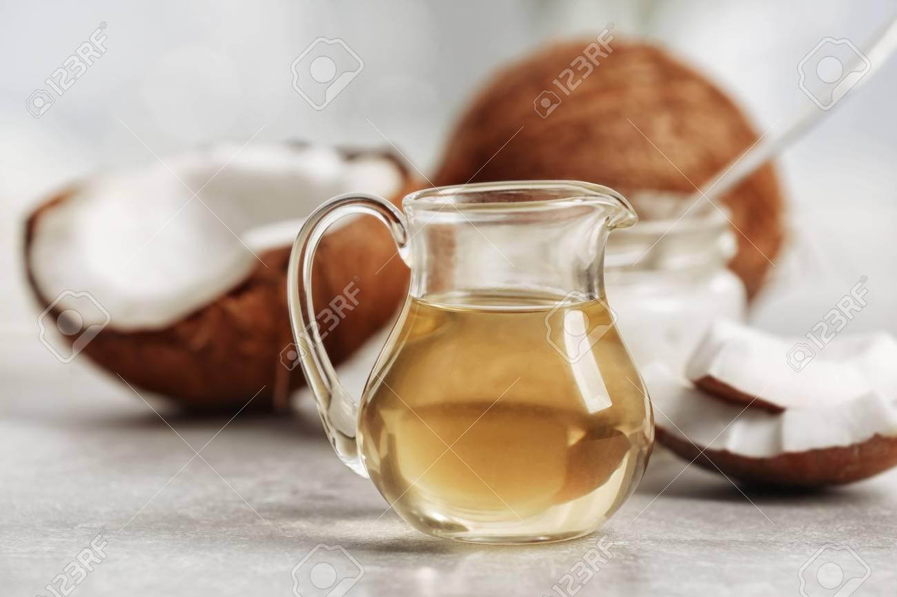 Fresh coconut oil in glassware on grey table - 97514461