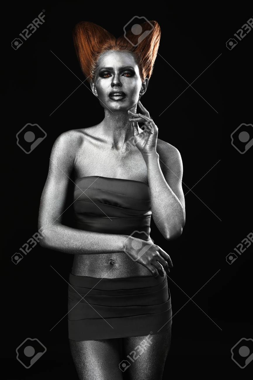 Beautiful young woman with amazing body-art as capricorn on dark