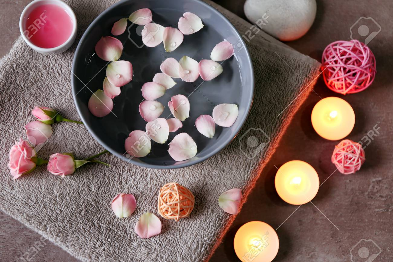 Beautiful spa composition of flower petals with water in bowl and candles on gray background - 97642824