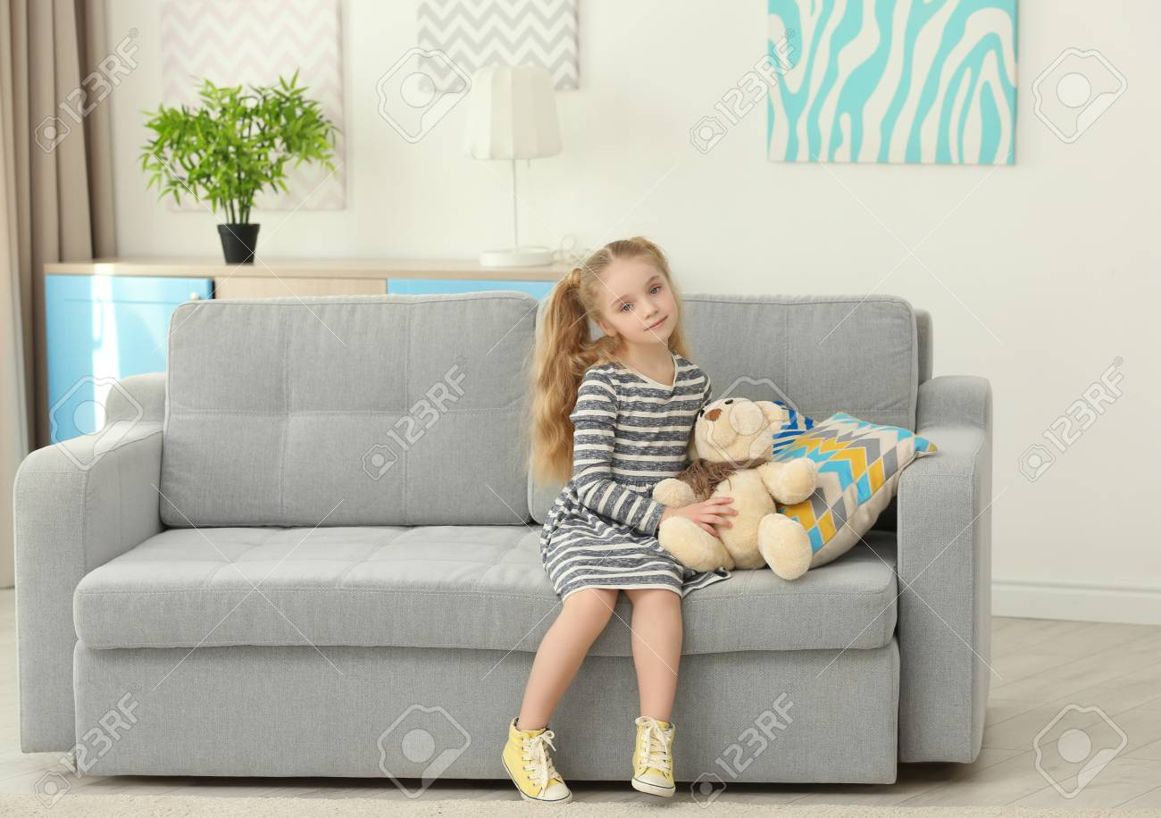 Wondrous Small Girl Sitting On Sofa With Teddy Bear In Living Room Alphanode Cool Chair Designs And Ideas Alphanodeonline